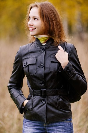 Young beautiful smiling woman with ladies handbag looks in profile against autumn park. photo