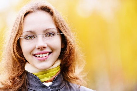 Young smiling girl-student in glasses close up against yellow autumn nature. photo