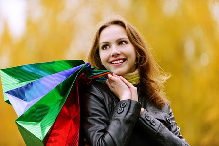 Young smiling student with purchases in packages comes back from shop against yellow autumn nature. Stock Photo