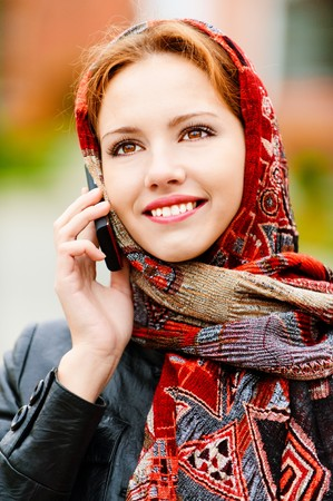 Young beautiful smiling woman in motley red headscarf talks on cellular telephone, against city structures. photo
