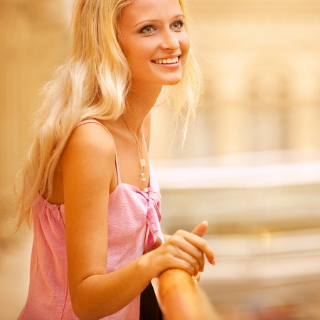 Beautiful girl leans against handrail in magnificent hall and laughs. photo