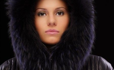 portrait of beautiful brunette girl in winter clothes on black photo