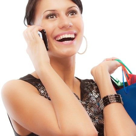 Charming girl with purchases speaks by phone, isolated on white background. Stock Photo - 8016486