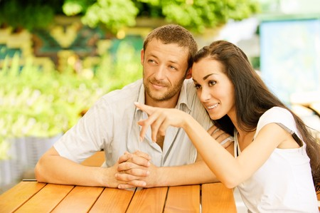 little table: Young couple sit at little table in summer cafe. Girl shows to young man forefinger on something in distance. Stock Photo