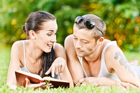 Beautiful couple lies on grass and reads book. photo