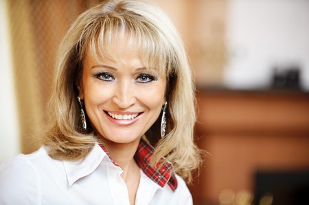 Portrait of mature smiling business woman close up against beautiful interior.