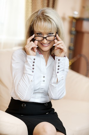 Mature smiling business woman sits on office sofa and holds fingers glasses. photo