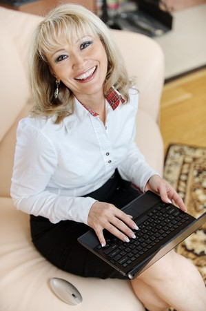 Mature smiling business woman sits on office sofa and works on black laptop. photo