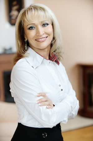 Portrait of beautiful smiling mature business woman in white shirt with crossed hands, against magnificent interior. Stock Photo