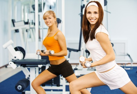 sports hall: Two beautiful smiling sportswomen do exercises with dumbbells in big sports hall. Stock Photo