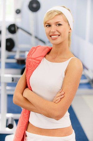 portrait of sporty blonde girl with red towel in gym