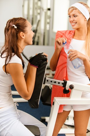 towel head: Two beautiful sportwomen make exercise on training apparatus
