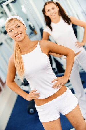 Two beautiful smiling sportswomen do exercises in big sports hall. Stock Photo - 8066190
