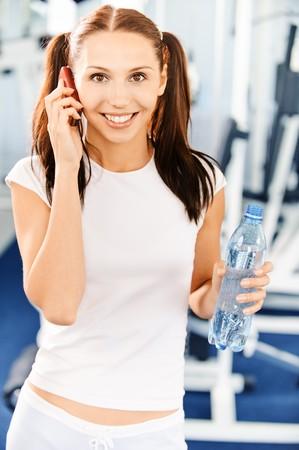 conversa: Young sonriente deportista Morena conversaciones por tel�fono m�vil contra grandes deportes sala.  Foto de archivo