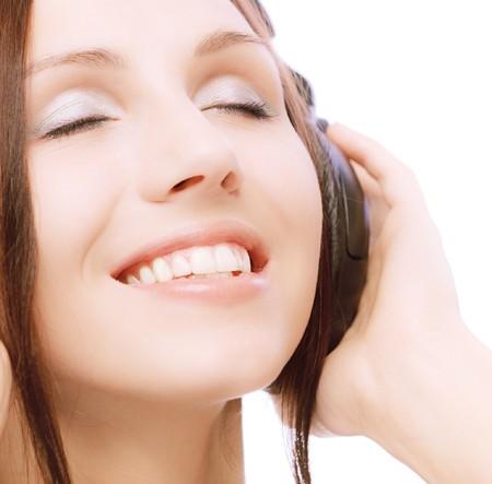 Lovely smiling girl in ear-phones, on white background. photo