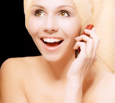 speaks: Woman after bath speaks on phone, on black background.