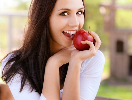 Smiling young woman bites red apple photo