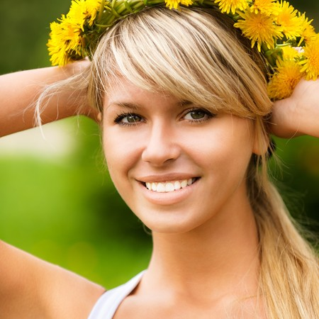 sexy blonde girl: Young woman in wreath from yellow dandelions.