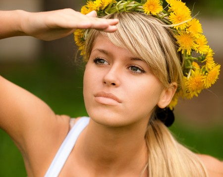 Young woman in wreath from yellow dandelions peers afar. Stock Photo - 8066016
