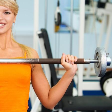 with orange and white body: Retrato de la mitad de chica rubia ejercicio en el gimnasio con peso