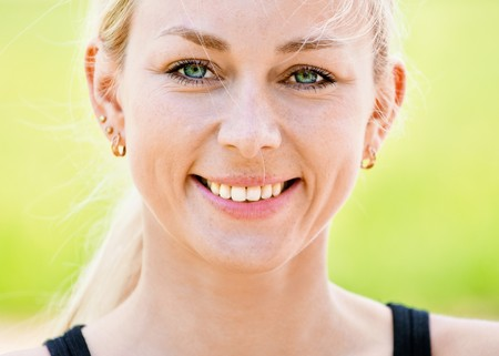 Portrait of young smiling woman against summer nature. photo
