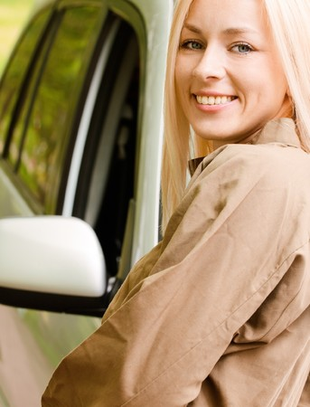cowl: Driver-woman of car stands about cowl and smiles against summer nature.