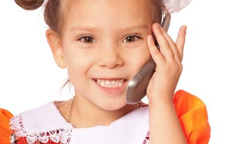 speaks: Little girl speaks on phone, isolated on white background. Stock Photo
