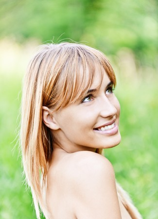 Beautiful lovely young woman with bared shoulders laughs against summer green nature. Stock Photo - 8065847