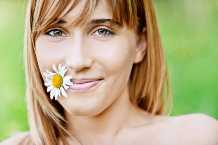 Portrait of beautiful young adult holding flower in mouth, against green summer nature. photo