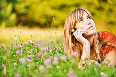 speaks: Beautiful young woman lies on green summer meadow among clover and talks by mobile phone.