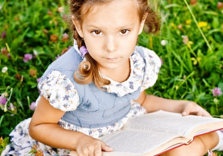 Beautiful little girl reads book, sitting on green lawn. Stock Photo - 8065875