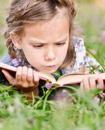 Beautiful little girl reads book, lying on green lawn. Stock Photo - 8065952
