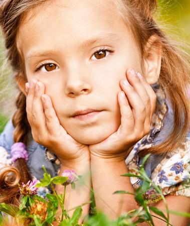Beautiful little girl lies on green lawn Stock Photo - 8065874