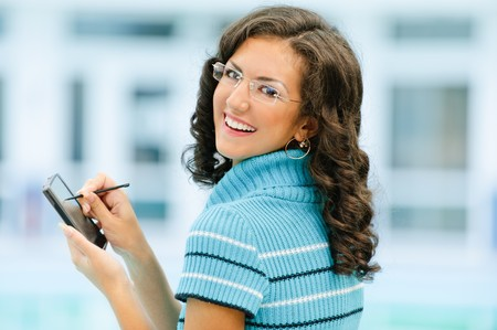 Beautiful smiling dark-haired woman in dark blue sweater and glasses writes with help stylus on pocket computer against spacious light hall. photo