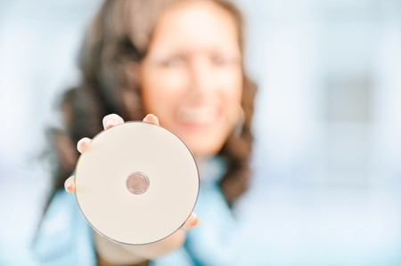 Young beautiful smiling dark-haired woman showing disk for data recording. Copy space. photo