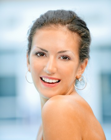 bared teeth: Beautiful dark-haired woman with bared houlders smiles. Stock Photo