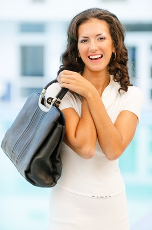 designer bag: Young beautiful brunette with flowing hair in white clothes has control over ladies handbag and laughs. Stock Photo