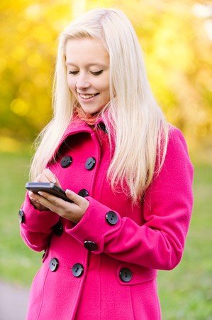 Beautiful smiling young blonde in red coat writes on pocket computer on autumn background. Stock Photo - 8090501