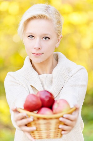 Bautiful fair-haired girl offer basket with red apples, against yellow foliage. photo