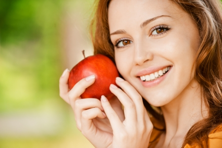 outdoor eating: Portrait of girl with red apple against green grass. Stock Photo
