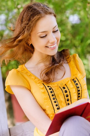 Charming long-haired girl-student reads red book photo