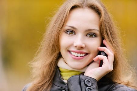 conversa: Sonrisas de joven hermosa y charlas sobre la telefon�a celular, cierre, contra la naturaleza oto�o amarillo.  Foto de archivo