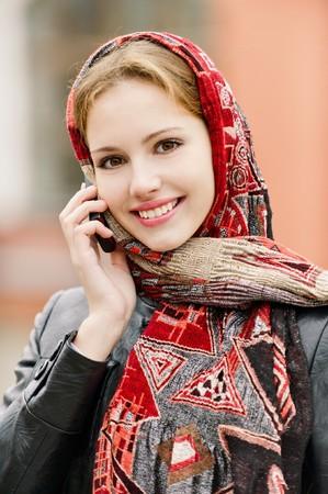 conversa: Joven hermosa mujer sonriente en las conversaciones de la abigarrada pa�uelo rojo sobre tel�fonos celulares, en comparaci�n con las estructuras de la ciudad.  Foto de archivo