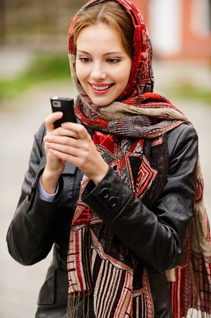 Young beautiful smiling woman in motley red headscarf dials number on cellular telephone, against city structures.