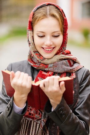 Smiling charming young woman in headscarf read red book on city background.