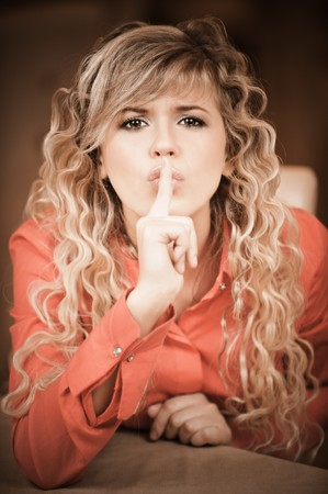Beautiful curly young woman in red clothes calls for silence, putting forefinger to lips. Stock Photo - 8175856