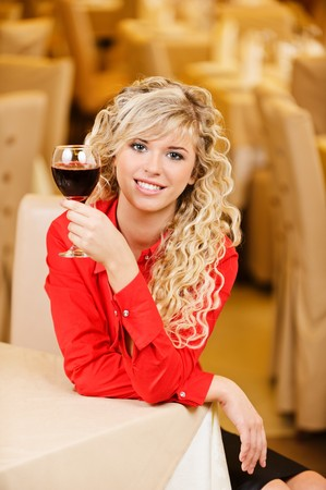 Charming smiling young woman in red clothes with red wine glass sits at magnificent restaurant. photo