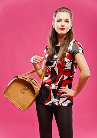 Young beautiful dark-haired girl has control over leather brown bag, on red background. photo