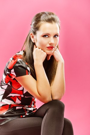 Young beautiful girl sits on chair, lean head on fists, on red background. photo