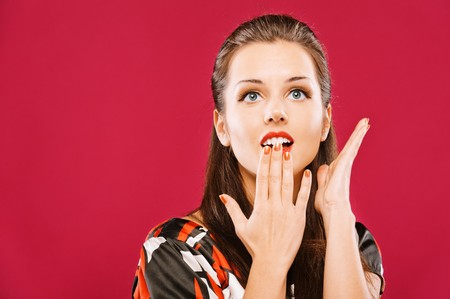 unexpectedness: Una mujer hermosa joven con asombro cubre boca con Palma, sobre fondo rojo.  Foto de archivo